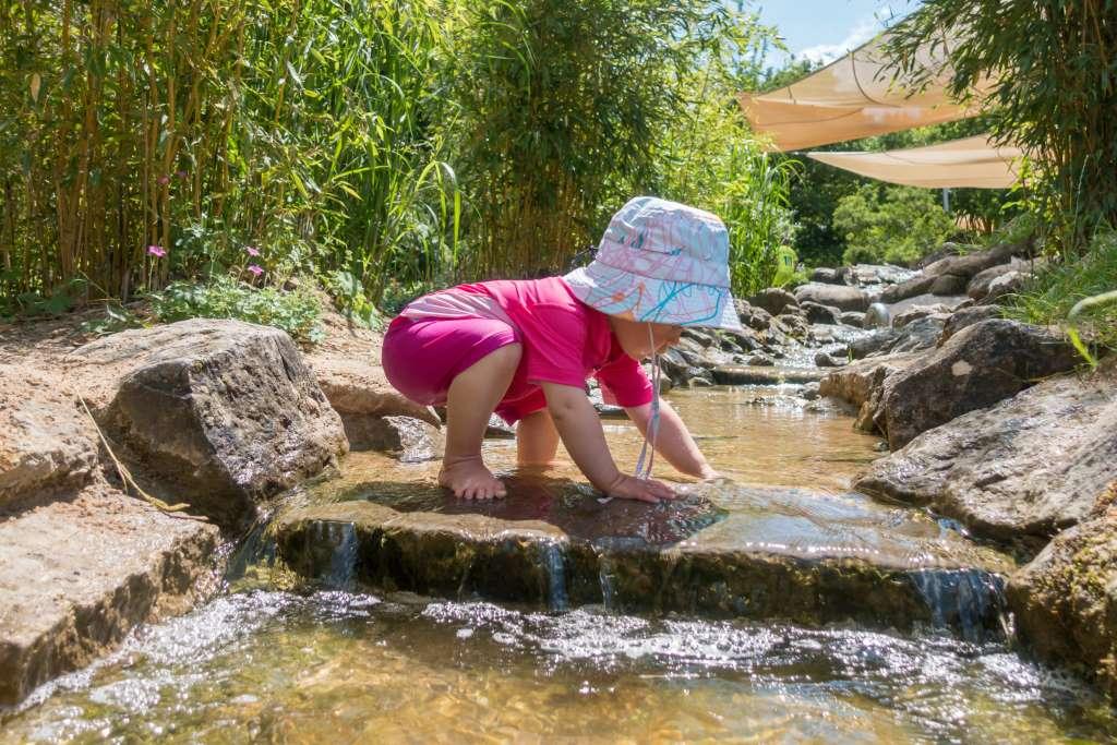 Spielen im Wasser mit UV-Schutzkleidung